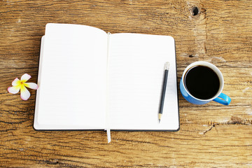 Notebook and black coffee on wooden table