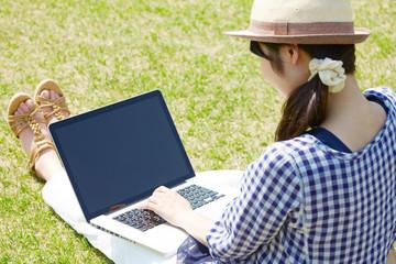 広場でパソコンを使う女性