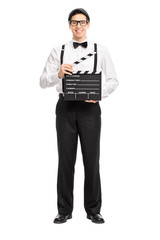 Young movie director holding a movie clapperboard