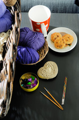 Wool kit, colorful clews, crochet hooks on the table.