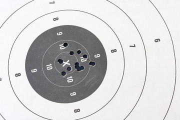 Close up of a shooting target and bullseye with bullet holes.