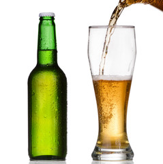 Pouring beer from bottle isolated on white