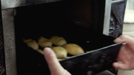 Woman Placing Tray Full Of Cookies In Oven