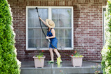Housewife washing the windows of her house - 82980535