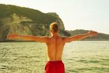 Mann mit Muskeln am Meer springt ins Wasser