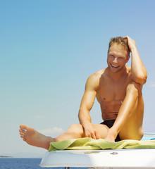 Sommer Urlaub: Mann in Badeshorts am Meer