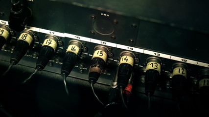 XLR Cables plugged into the back of a mixing console desk
