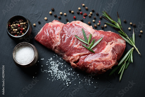 Fotografiet Raw ribeye steak with seasonings, close-up, studio shot