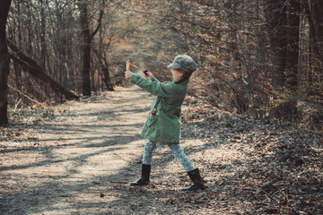 little girl playing with a slingshot