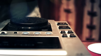 DJ spinning and touching CDJ console mixer faders and knobs