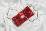 Red lacquer bag lying on a white silk