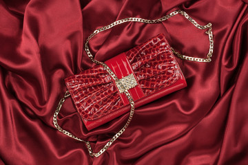 Red lacquer bag lying on a red silk