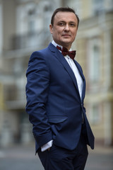 Stylish man in a blue suit with butterfly tie