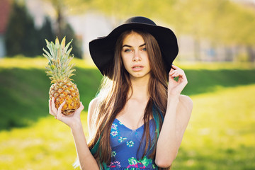 Gorgeous boho young woman with pineapple and fedora hat