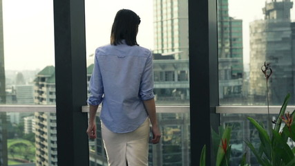 Successful businesswoman walk and look at cityscape
