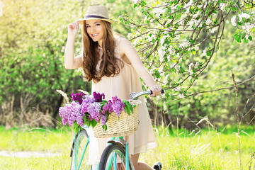 Beautiful girl in a hat on a vintage bike