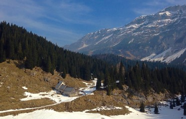 Alpine scenery with mountain hut and mountains in winter
