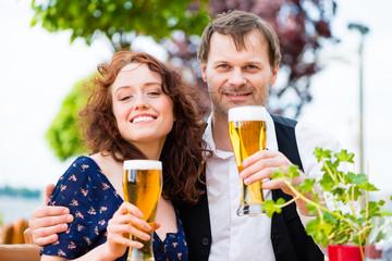 Verliebtes Paar prosten mit Bier im Biergarten