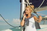 Schöne junge blonde Frau am Meer mit Segelboot