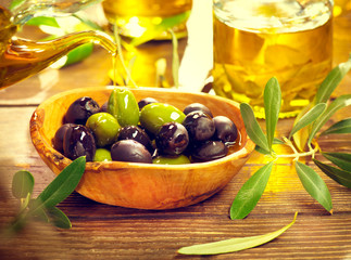 Olives and virgin olive oil on the wooden table