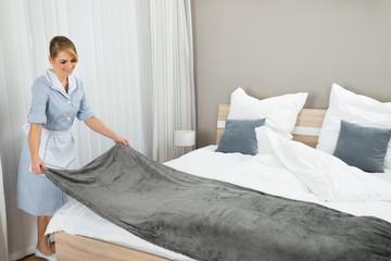 Female Housekeeping Worker Making Bed
