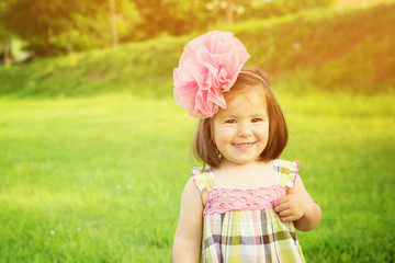 Cute little girl with big pink tulle flower headband smiling