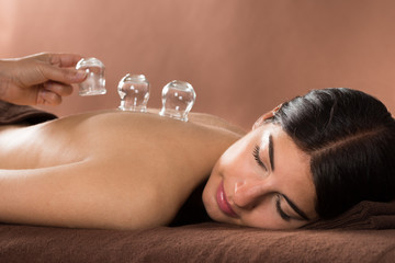 Woman Getting Cupping Treatment At Spa