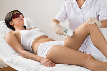 Person Giving Laser Therapy To Woman
