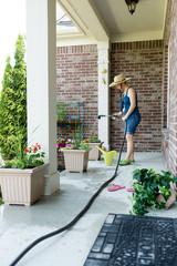 Woman gardener standing watering new plants