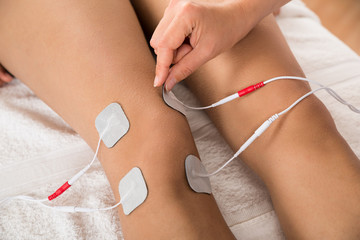Therapist Placing Electrodes On Woman's Knee