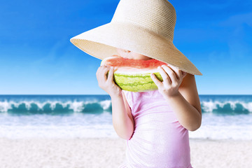 Attractive child eats a watermelon