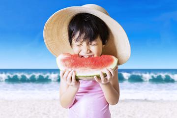 Child bites a watermelon at coast