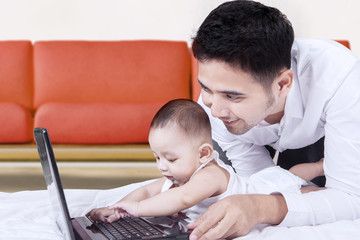 Male toddler playing laptop with his dad