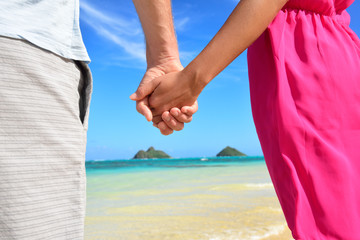 Beach couple in love holding hands on honeymoon