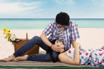 Young man caress his girlfriend at beach