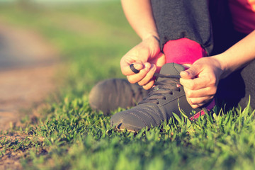 Girl tying shoelaces shoes sitting on the grass