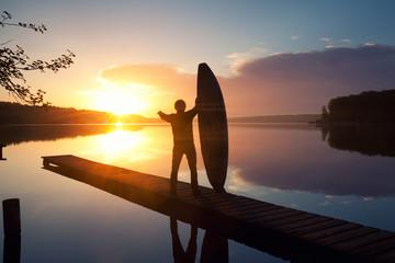 Surfer mit Surfbrett am See