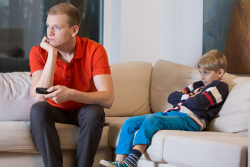 Bored child and father is watching TV