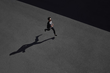 Running man sprinting for success on run. Top view athlete