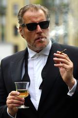Mann im Smoking mit Glas und Zigarette
