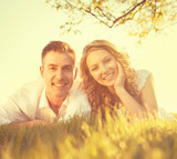 Happy smiling couple together relaxing on grass in a park