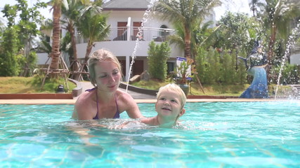 blonde little girl learns swim and splashes with mother in pool