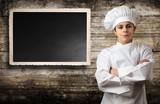 giovane chef con lavagna menù e fondo legno