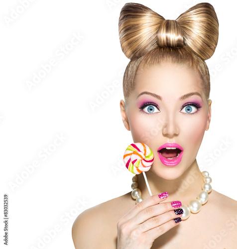 zabawna-dziewczyna-z-kokarda-fryzure-jedzenie-kolorowy-lollipop