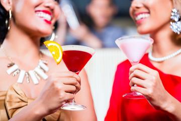 Asian women drinking cocktails in fancy bar