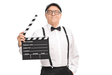 Confident mature movie director holding a clapperboard