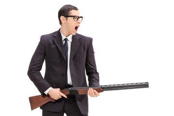 Angry man holding a rifle and shouting