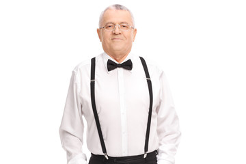 Elegant cheerful senior standing with his hands in his pockets