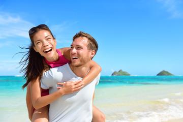 Beach couple having fun laughing on Hawaii holiday