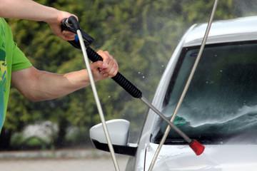 Mann reinigt Front Auto mit Hochdruckreiniger